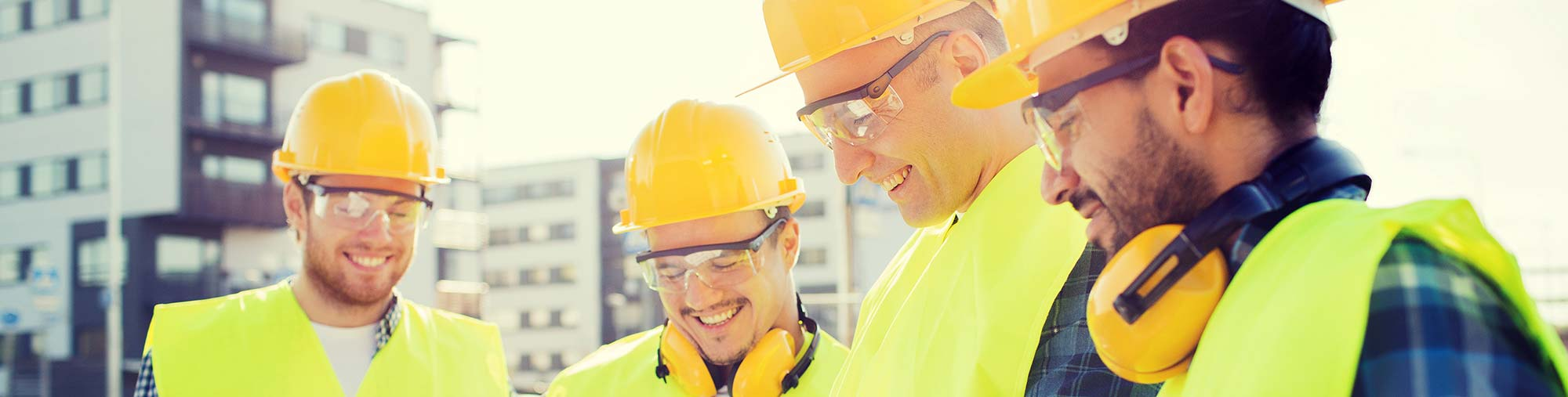 Workers in safety gear smiling